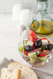 Greek salad  with bread on the white scratched table vertical Royalty Free Stock Photo
