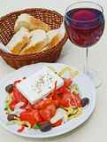 Greek salad with bread and wine. An image of a table with a plate of colorful Greek salad, a glass of red wine and some sliced Cretan bread in a wicker basket Stock Images
