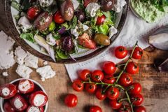 Greek salad with cherry tomatoes, onions, antipasti and feta cheese on wooden table top view royalty free stock images