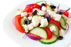 Greek Salad close up on white plate isolated on white Stock Images