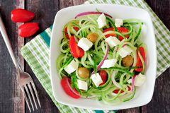 Greek Salad with cucumber noodles above view on dark wood Stock Photos