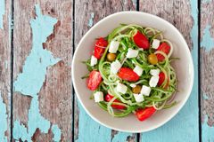 Greek Salad with cucumber noodles, overhead view on rustic wood Stock Photos