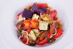 Greek salad eggplant feta thyme, red onion, basil tomatoes  plate isolated white background arugula Stock Images
