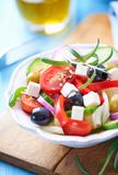 Greek salad with feta cheese, cherry tomatoes, red pepper, black and green olives, cucumber and fresh rosemary. stock images