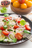 Greek salad with feta cheese on a plate, vertical Stock Photo