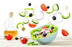 Greek Salad with flying ingredients to prepare it. On a white background Royalty Free Stock Image