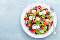 Greek salad of fresh cucumber, tomato, sweet pepper, lettuce, red onion, feta cheese and olives with olive oil. Top view stock image