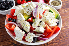 Greek salad with fresh sweet pepper, red onion, orange cherry tomatoes, cucumber, black olives and feta chees drizzled Royalty Free Stock Image