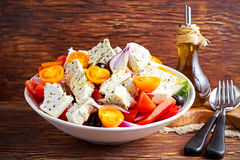 Greek salad with fresh sweet pepper, red onion, orange cherry tomatoes, cucumber, black olives and feta chees drizzled Royalty Free Stock Photography