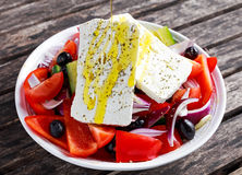 Greek salad with fresh sweet pepper, red onion, orange cherry tomatoes, cucumber, black olives and feta chees drizzled Stock Images