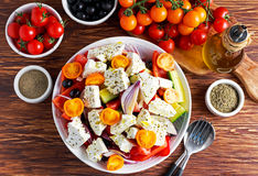 Greek salad with fresh sweet pepper, red onion, orange cherry tomatoes, cucumber, black olives and feta chees drizzled Stock Photo
