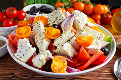 Greek salad with fresh sweet pepper, red onion, orange cherry tomatoes, cucumber, black olives and feta chees drizzled Royalty Free Stock Images