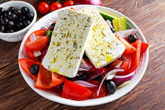 Greek salad with fresh sweet pepper, red onion, orange cherry tomatoes, cucumber, black olives and feta chees drizzled Stock Image
