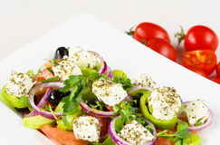 Greek salad with fresh tomato, cucumber, red onion, basil, feta cheese, black olives, Italian herbs and olive oil in white dish on Stock Image