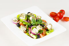 Greek salad with fresh tomato, cucumber, red onion, basil, feta cheese, black olives, Italian herbs and olive oil in white dish on Stock Images