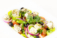 Greek salad with fresh tomato, cucumber, red onion, basil, feta cheese, black olives, Italian herbs and olive oil in white dish on Royalty Free Stock Photography
