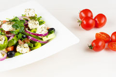 Greek salad with fresh tomato, cucumber, red onion, basil, feta cheese, black olives, Italian herbs and olive oil in white dish on Stock Photography