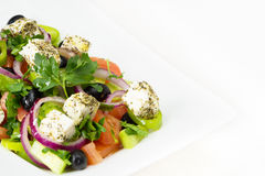 Greek salad with fresh tomato, cucumber, red onion, basil, feta cheese, black olives, Italian herbs and olive oil in white dish on Stock Photos