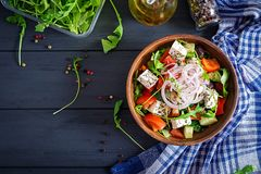 Greek salad with fresh tomato, cucumber, red onion, basil, feta cheese. Black olives and Italian herbs. Top view royalty free stock image