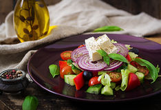 Greek salad with fresh tomato, cucumber, red onion, basil, lettuce, feta cheese, black olives and a Italian herbs Royalty Free Stock Photos