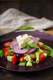 Greek salad with fresh tomato, cucumber, red onion, basil, lettuce, feta cheese, black olives and a Italian herbs Stock Photography