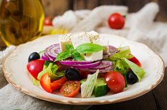 Greek salad with fresh tomato, cucumber, red onion, basil, lettuce, feta cheese, black olives and a Italian herbs Royalty Free Stock Photography