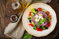Greek salad with fresh tomato, cucumber, red onion, basil, lettuce, feta cheese, black olives and a Italian herbs on plate. Royalty Free Stock Photography