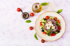 Greek salad with fresh tomato, cucumber, red onion, basil, lettuce, feta cheese, black olives and a Italian herbs Royalty Free Stock Photo