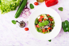 Greek salad with fresh tomato, cucumber, red onion, basil, lettuce, feta cheese, black olives and Italian herbs. Royalty Free Stock Photo