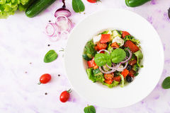 Greek salad with fresh tomato, cucumber, red onion, basil, lettuce, feta cheese, black olives and Italian herbs. Stock Photography