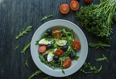 Greek salad with fresh tomatoes, arugula, eggs, olives with olive oil on a dark wood background. Healthy food. Veggie dish stock images