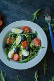 Greek salad with fresh tomatoes, arugula, eggs, olives with olive oil on a dark wood background. Healthy food. Veggie dish stock photos