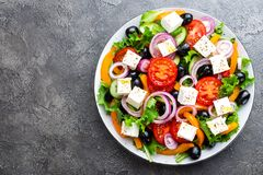 Greek salad. Fresh vegetable salad with tomato, onion, cucumbers, pepper, olives, lettuce and feta cheese. Greek salad. On plate royalty free stock photos