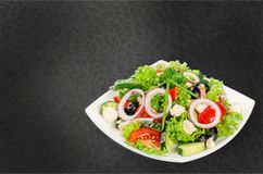 Greek salad with fresh vegetables on dark table royalty free stock image