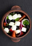 Greek salad with fresh vegetables, feta cheese and black olives on a dark background. Top view stock photo