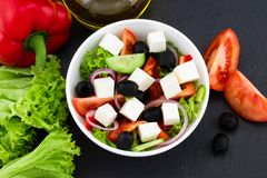 Greek salad with fresh vegetables, feta cheese and black olives on a dark background. Top view royalty free stock photography