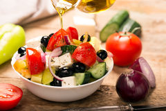Greek salad with fresh vegetables. Greek salad : fresh vegetables, feta cheese and black olives. Pouring oil Stock Photography
