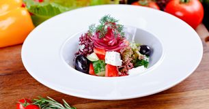 Greek salad with fresh vegetables, feta cheese and black olives on white plate. Close up stock images