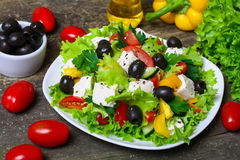 Greek salad with fresh vegetables, feta cheese and black olives on a wooden background Royalty Free Stock Photography