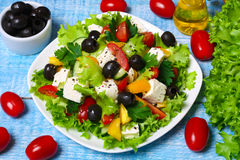 Greek salad with fresh vegetables, feta cheese and black olives on a wooden background Royalty Free Stock Images