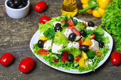 Greek salad with fresh vegetables, feta cheese and black olives on a wooden background Stock Images