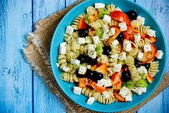 Greek salad with fresh vegetables, feta cheese, pasta and black olives. On blue wooden background top view royalty free stock image