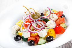 Greek salad with fresh vegetables, olives and feta cheese on wooden background close up. Stock Photos