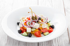 Greek salad with fresh vegetables, olives and feta cheese on wooden background close up Stock Image