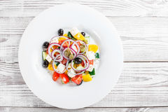 Greek salad with fresh vegetables, olives and feta cheese on wooden background close up. Top view Stock Photography
