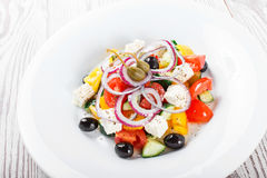 Greek salad with fresh vegetables, olives and feta cheese on wooden background. Close up. Top view Stock Image