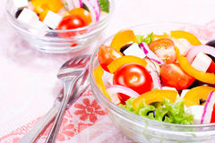 Greek salad. With fresh vegetables on the table in transparent salad bowl Stock Images