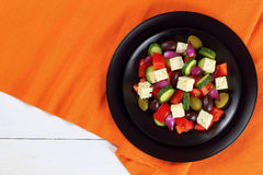 Greek salad with fresh vegetables, top view. Delicious Greek salad with fresh vegetables, feta cheese green and kalamata olives, red onion bulbs on black plates Royalty Free Stock Photos