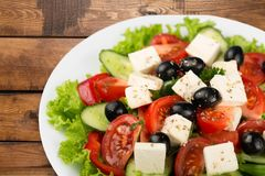 Greek salad with fresh vegetables on wooden table stock photography