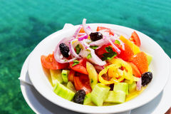 Greek salad in front of Mediterranean sea Stock Photo